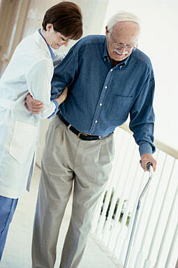 Older man with a cane being helped by a doctor