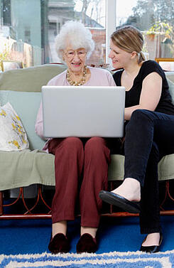 Young woman showing her grandmother how to use a laptop