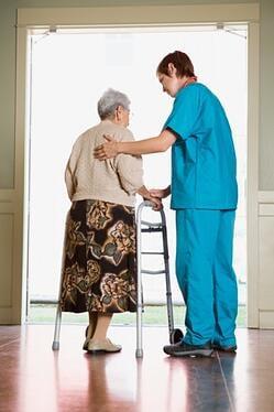 Elderly nursing home resident standing with a nurse