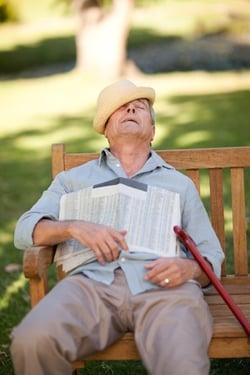 senior man asleep on bench