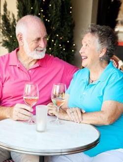 senior couple enjoying glass of wine at outdoor cafe